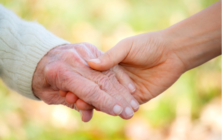 A young personing holding the hand of a senior showing the concept of support for the elderly in a senior living community